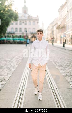 Summer day, walk in the city concept. Front view of young stylish Caucasian man dressed in white shirt and beige pants, standing on city street