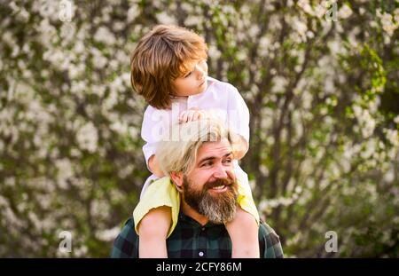 Happy family. Fathers day. Child having fun with dad. Little boy and father in nature background. Springtime. Hipster piggybacking baby. Bearded brutal man good father. Dad and son. Best dad ever.