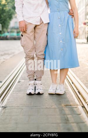 Cropped image of legs of lovely stylish young couple in love, woman in blue dress and man in beige pants, standing on the pavement road and tram track - Stock Photo