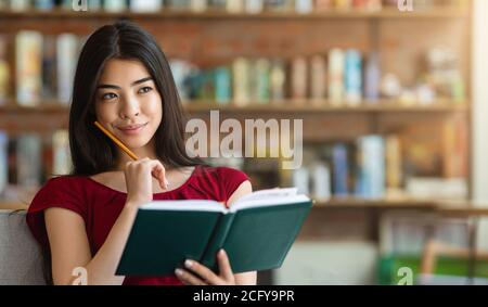 Thinking About Future Plans. Pensive Asian Girl Sitting With Notepad In Cafe
