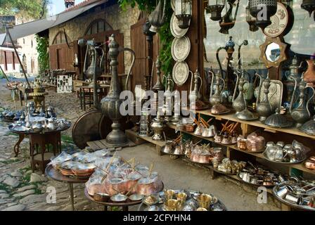 A display of traditional Turkish souvenirs of bronze and copper handcrafted cookware and souvenir hanging from the wall on the pavement waiting for - Stock Photo