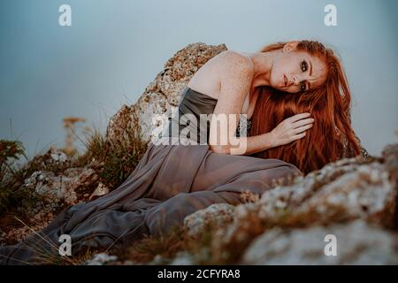 beautiful furious scandinavian warrior ginger woman in grey dress with metal chain mail. Woman is a Viking. Fantasy. Book Cover