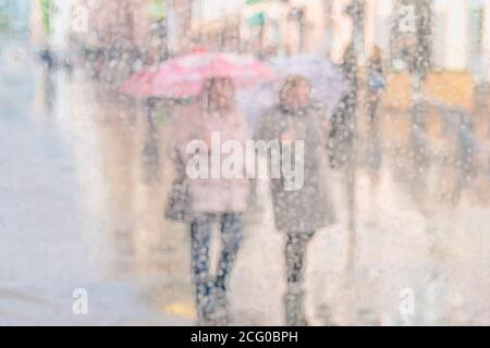 Light pastel blurred background with silhouettes of two girls, girlfriends under umbrellas on a rainy day, city life, bokeh. Concept of modern urban