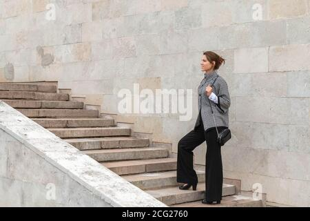 Businesswoman climbing up a concrete staircase on city wall background. Successful woman concept. Copy space - Stock Photo