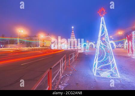 City view of the Theater and the main Christmas tree of the city in the evening the city in the night illumination. Beautiful traces of headlights of cars on the road
