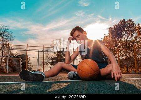 Sports and basketball. A young teenager in a blue tracksuit poses with a ball while sitting on a sports field. Blue sky in the background. Copy space.