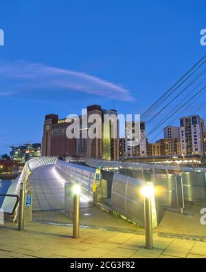 Looking up the path and cycleway of the Gateshead Millennium Bridge towards the Baltic Art Centre at dusk. - Stock Photo