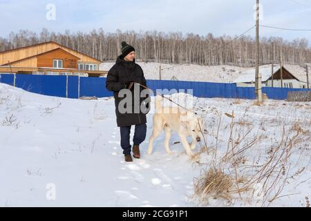 A young man walks with a big dog on a winter street in the background of village apartment buildings. - Stock Photo