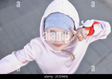 Little girl with blue eyes in warm clothes and hood looks up and greets with gesture. - Stock Photo