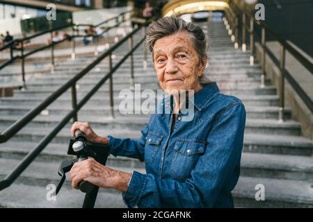 90 year old woman with gray hair, wrinkles, progressive and active uses modern electric transport scooter. Lady pensioner use eco friendly city