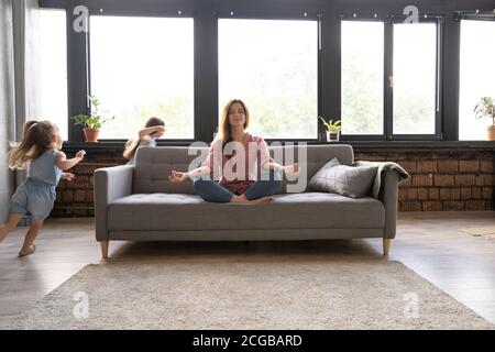 Calm woman concentrating on yoga exercises on couch at home while two noisy kids laughing, running