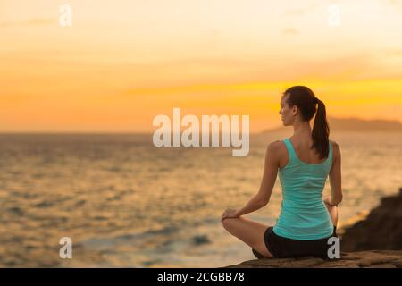 Fit relaxed woman meditating at peace on the beach with a beautiful view of the ocean during sunset. Health, yoga and harmony.