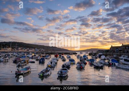 Lyme Regis, Dorset, UK. 10th Sep, 2020. UK Weather: Boats moored in the Cobb harbour light up under a beautiful autumnal sunrise on a chilly morning at the coastal resort of Lyme Regis as high pressure moves into the region bringing dry and settled conditions ahead of a prediccted mini-heatwave. Credit: Celia McMahon/Alamy Live News