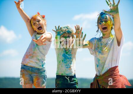 Portrait of a beautiful kids showing colorful colored hands. Happy childhood. Emotional cheerful excited children.