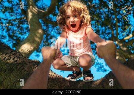 Insurance kids. Toddler kid learning to climb having fun in garden outdoors. Health care insurance concept for family and children medical healthcare