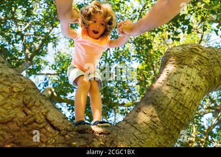 Father helping son climb a tree. Happy kid climbing up tree and having fun in summer park. Fathers hand. Father teaching son climb tree.
