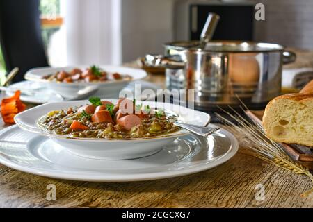 lentil soup with hot dogs on a white plate served on a table with wooden background - Stock Photo