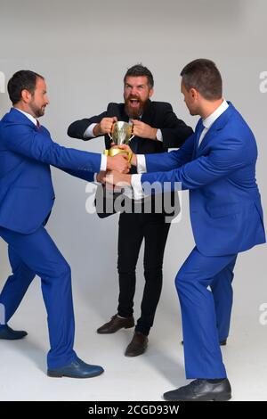 Businessmen with mad faces in formal suits on grey background. Business rivalry and competition concept. Company leaders fight for business leadership. Coworkers tear winners cup as symbol of success - Stock Photo