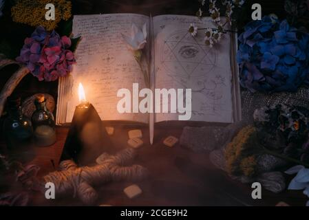Open old book with magic spells, runes, black candle and herbs on witch table. Occult, esoteric, divination and wicca concept. Halloween vintage backg