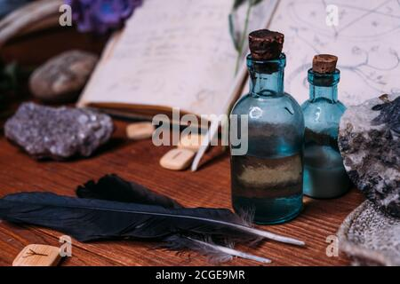 Magic potion bottle. Witchcraft halloween concept with potions, herbs and occult equipment. Magical still life with copy space on a dark background.