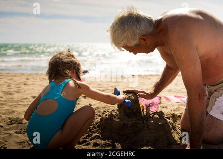 Caucasian grandfather and granddaughter playing with sand, building a sand castle together on the beach. - Stock Photo