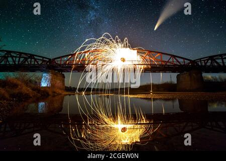 Spinning steel wool in abstract circle, firework showers of bright yellow sparks on long bridge reflected in river water under dark night starry sky. - Stock Photo