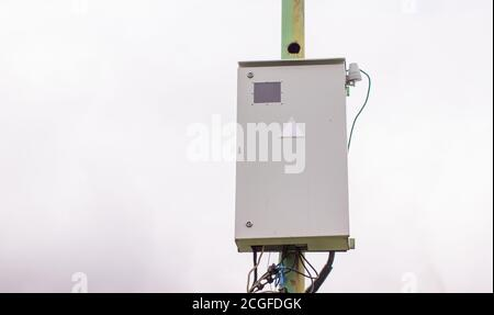 White electric box on a pole outside the house. - Stock Photo