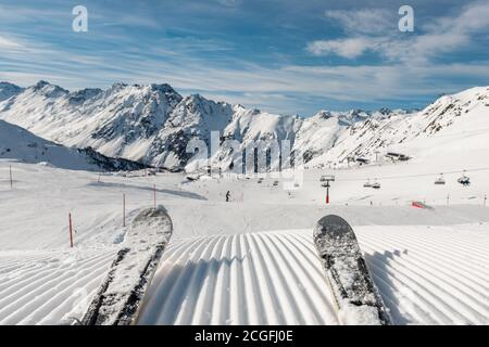 Panorama point of view skier legs on downhill start straight line rows freshly prepared groomed ski slope piste on bright day blue sky background