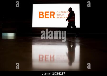 08 September 2020, Brandenburg, Schönefeld: A man walks 'Willy Brandt' (BER) in front of an illuminated banner with the BER logo during a tour of the capital airport Berlin Brandenburg. The Capital Airport is scheduled to open on 31 October 2020. Photo: Christoph Soeder/dpa