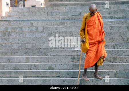 bodh gaya bihar india on april 29th 2018 : old buddhist monk walking down through stairs at mahabodhi temple complex bihar india. - Stock Photo