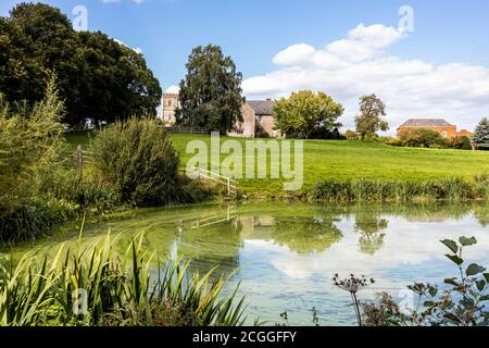 Maisemore Court and St Giles church viewed across the lake in the Severn Vale village of Maisemore, Gloucestershire UK