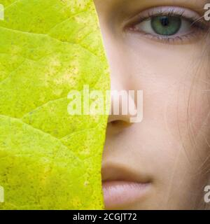 Beauty young blonde women with green eyes without make up. Teen girl model and big green leaf. Concept of Spa, skin care, wellness, nature organic cos - Stock Photo