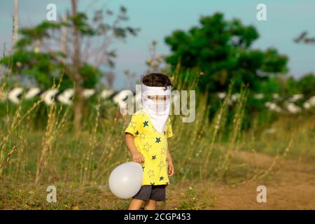 To avoid the corona virus, a little child covered with a mouth full of homemade face masks played with Balloon in the parking lot by the ecr road in c - Stock Photo
