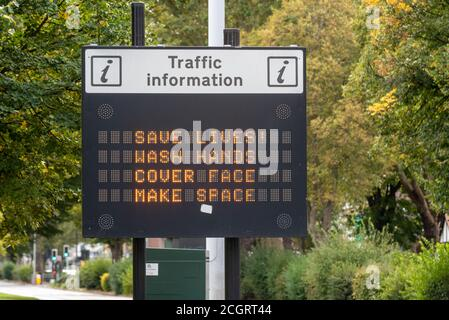 COVID-19 slogan message on traffic information matrix sign. Save lives, wash hands, cover face, make space, message. Southend on Sea, Essex, UK - Stock Photo