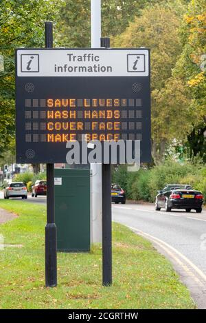 COVID-19 slogan message on traffic information matrix sign. Save lives, wash hands, cover face, make space. Cars on road to Southend on Sea, Essex, UK - Stock Photo