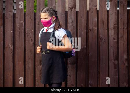A 10 year old schoolgirl wearing a school uniform and pink face mask and looking away. - Stock Photo