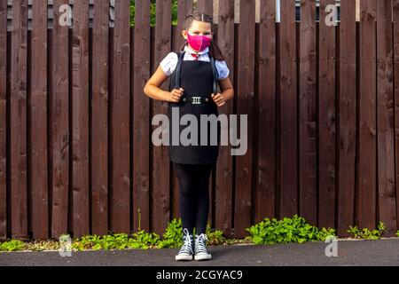 A 10 year old schoolgirl wearing a school uniform and pink face mask and looking towards camera. - Stock Photo