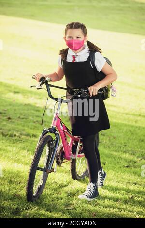 A 10 year old schoolgirl wearing a school uniform and face mask and standing next to her bicycle - Stock Photo