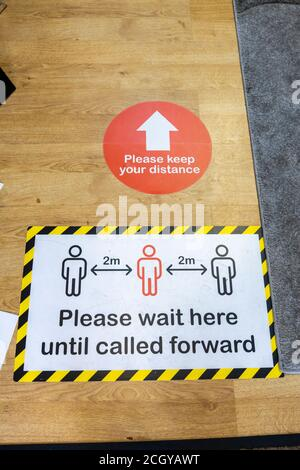 Intructions in a shop entrance: please wait here until called forward, keep your distance. Sidmouth, a coastal town in Devon - Stock Photo