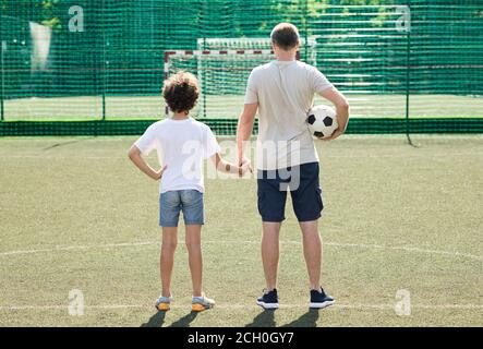 Dad posing with little boy on football pitch, back view - Stock Photo