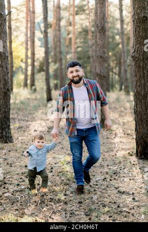 Full length outdoor portrait of handsome bearded young man father, walking in pine autumn forest together with his little adorable child son - Stock Photo