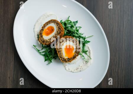 Scotch Egg Cut in Half with Golden Yolk served on a Plate and Rocket Salad - Stock Photo