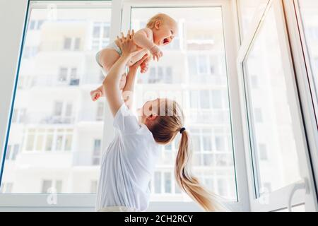 Mother playing with newborn baby son at home. Woman tossing kid up on balcony. Happy infant wearing diaper - Stock Photo
