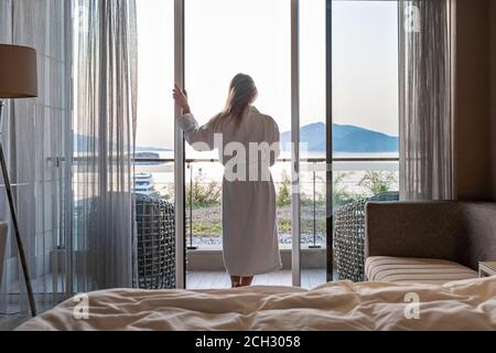 Beautiful woman from back in bathrobe standing on terrace of hotel room with Sea View morning sunrise - Stock Photo