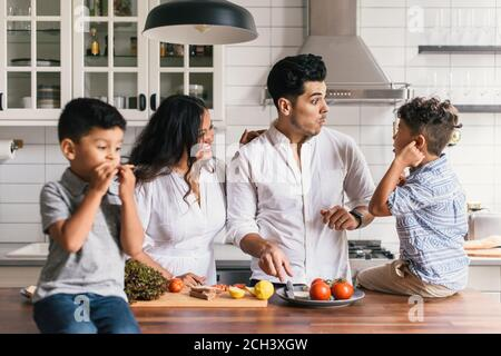 Family making funny faces at each other while preparing lunch meal