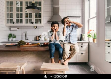 Two young boys making funny faces while in the kitchen with lunch