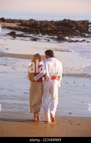 Couple enjoying romantic moments walking on sandy shore along Southern California coast in sunset light - Stock Photo