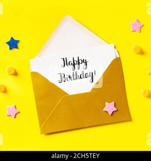 Happy Birthday card in a golden envelope, overhead square shot on a yellow background with glitter stars - Stock Photo