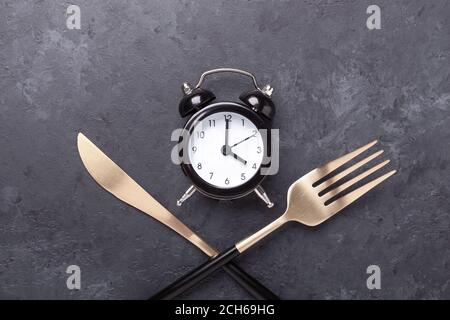 Black alarm clock, fork, knife on dark stone background. Intermittent fasting concept - Image