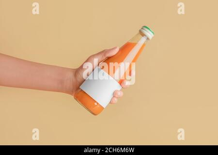 Female hand with bottle of juice on color background